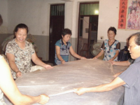 手工蠶絲被的制作過程 須經過燒煮 剝繭 曬絲綿 拉絲被幾個過程。